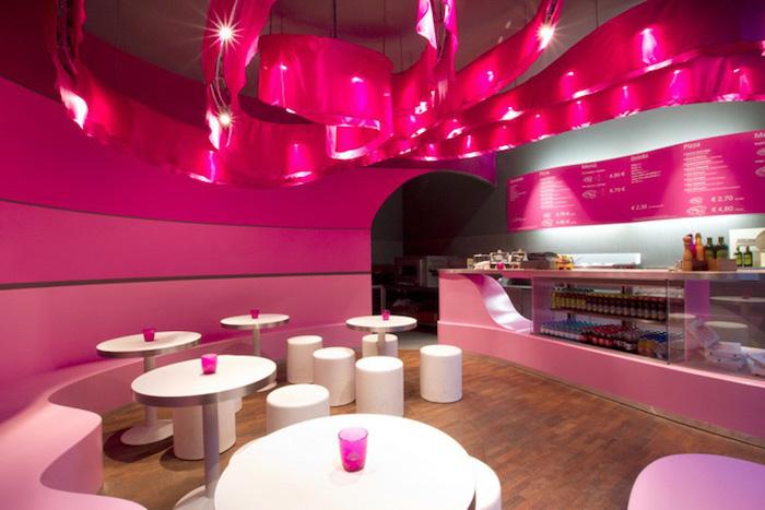 couleur framboise, bar en verre et comptoir rose, murs peints en nuances roses, table ronde avec tabourets blancs