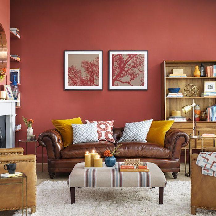 peinture rouge sur le mur dans un salon, moderne aux accents jaunes, canapé et fauteuils en cuir avec des coussins jaunes et blancs, tapis blanc, bibliothèque en bois, deco romantique, cheminée