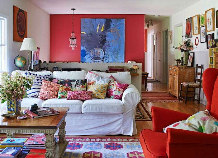 peinture rouge sur un mur d accent, canapé blanc, fauteuil rouge, coussins et tapis colorés, motifs floraux, deco mur de cadres