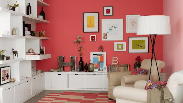 peinture rouge tirant vers le rose saumon dans un salon moderne avec riche deco murale de cadres et accessoires deco, bibliothèque et meubles de rangement blancs
