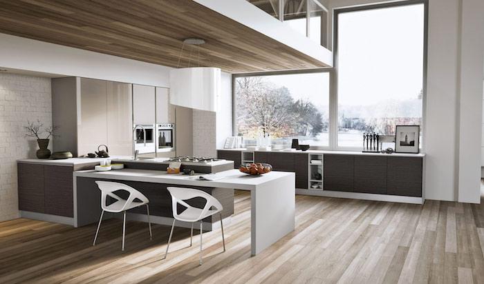meuble haut cuisine, murs blancs avec déco en briques, chaises blanches, sol en bois clair