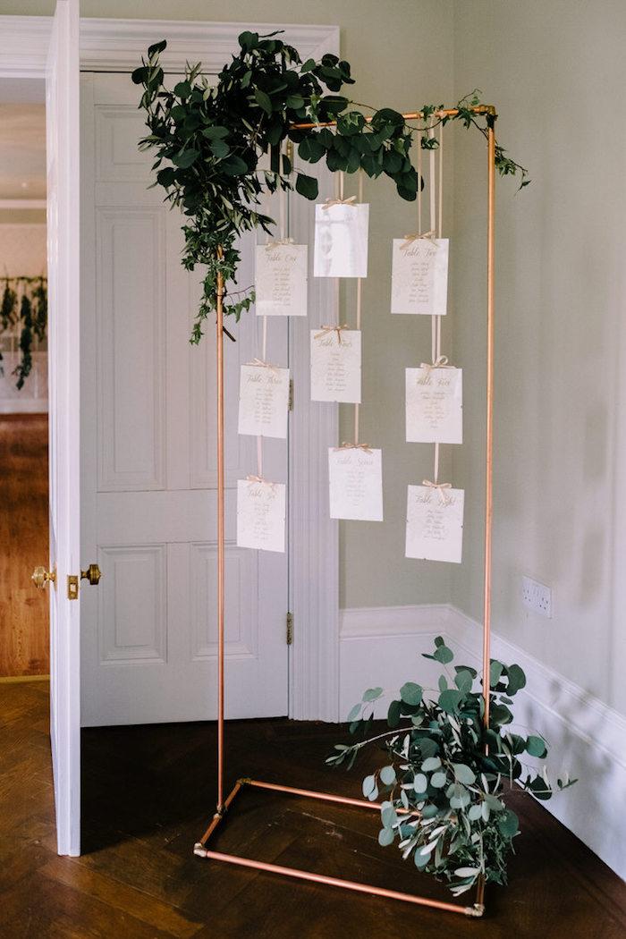 plan de table original en support en tubes de cuivre et listes invités blanches suspendues à des ficelles avec décoration branches vertes