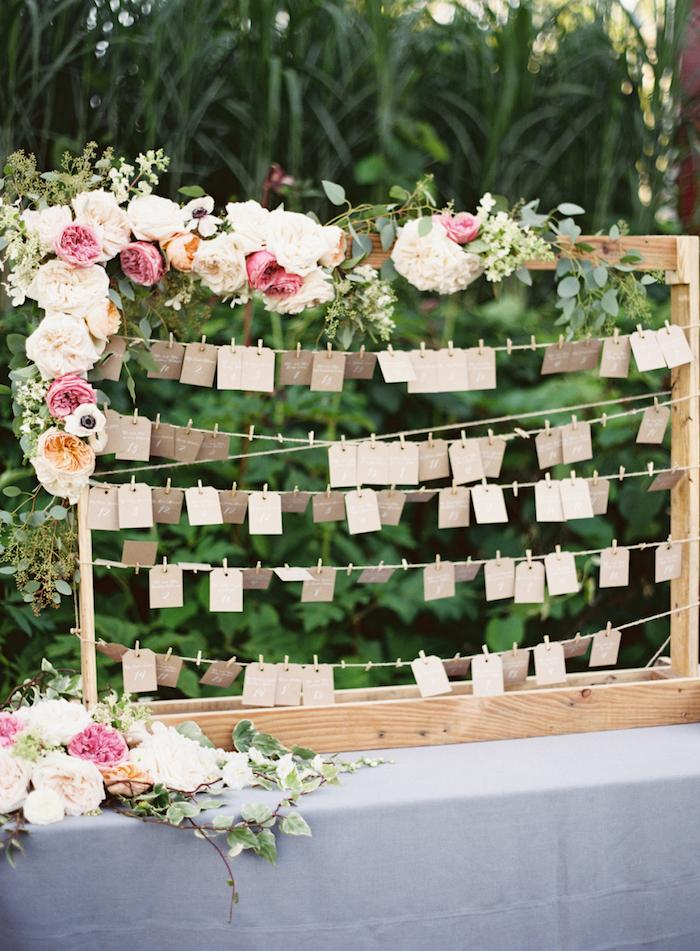 plan de table mariahe en cadre en bois avec des étiquettes en papier kraft avec des noms invités pour trouver sa place, guirlande de fleurs fraîches