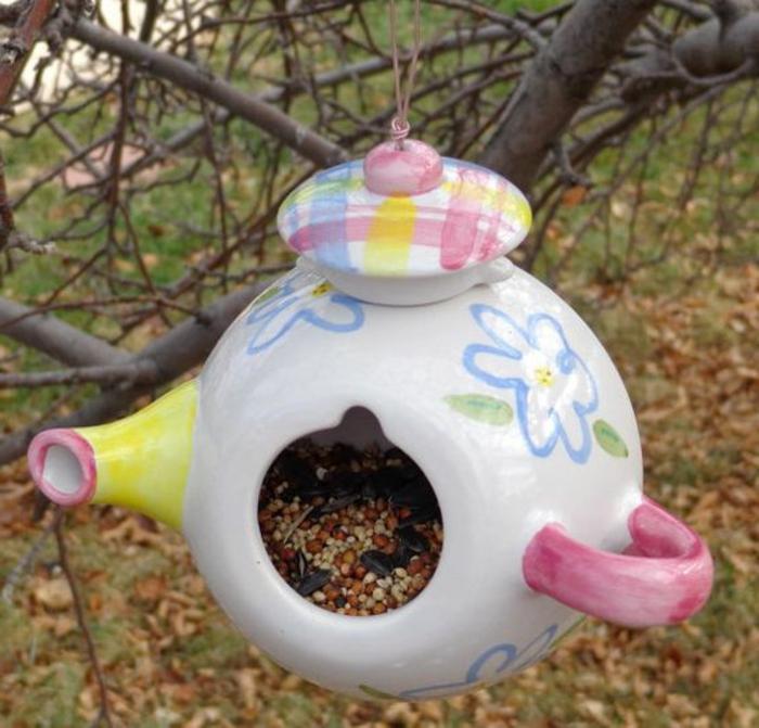 plan mangeoire oiseaux gratuit, théière en couleurs douces remplie de nourriture accroché à un arbre