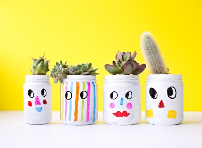 de petits pots en verre repeints en blanc, avec des dessins enfant dessus, transformées en pots de fleurs simples