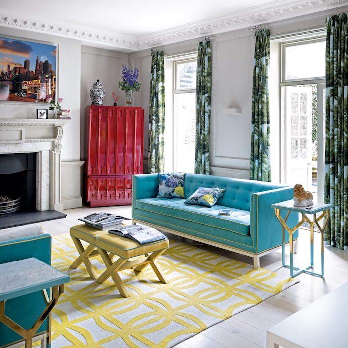 association de couleur, buffet rouge, canapé et fauteul bleu, tables basses jaunes, tapis gris et jaune, rideaux bleue t vert, cheminée aspect marbre