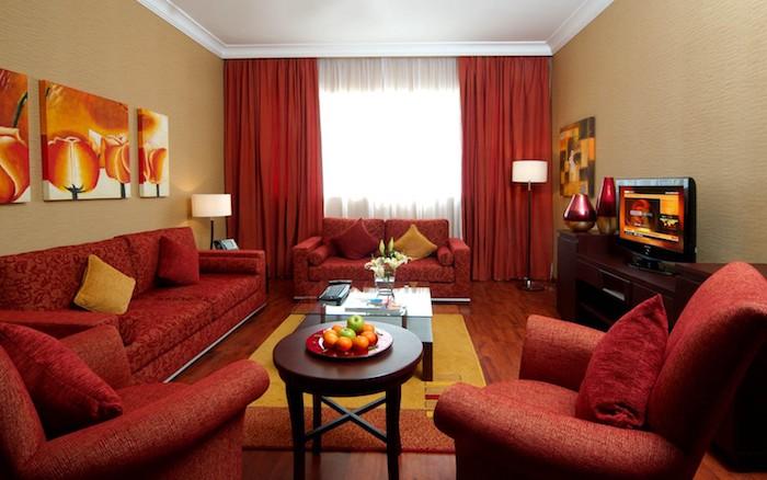association de couleur, rouge et beige foncé, canapés et fauteuils rouges, tapis jaune et orange, meuble tv marron