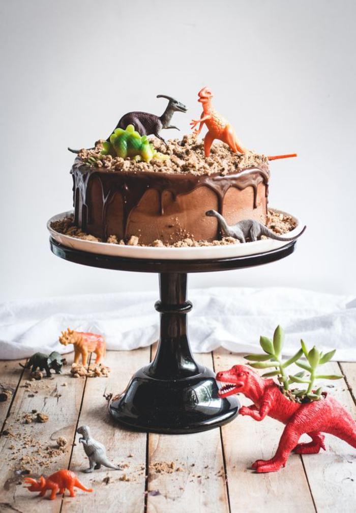recette de gateau au chocolat anniversaire sur le thème sur dinosaure décoré de figurines en plastique et de biscuits écrasés