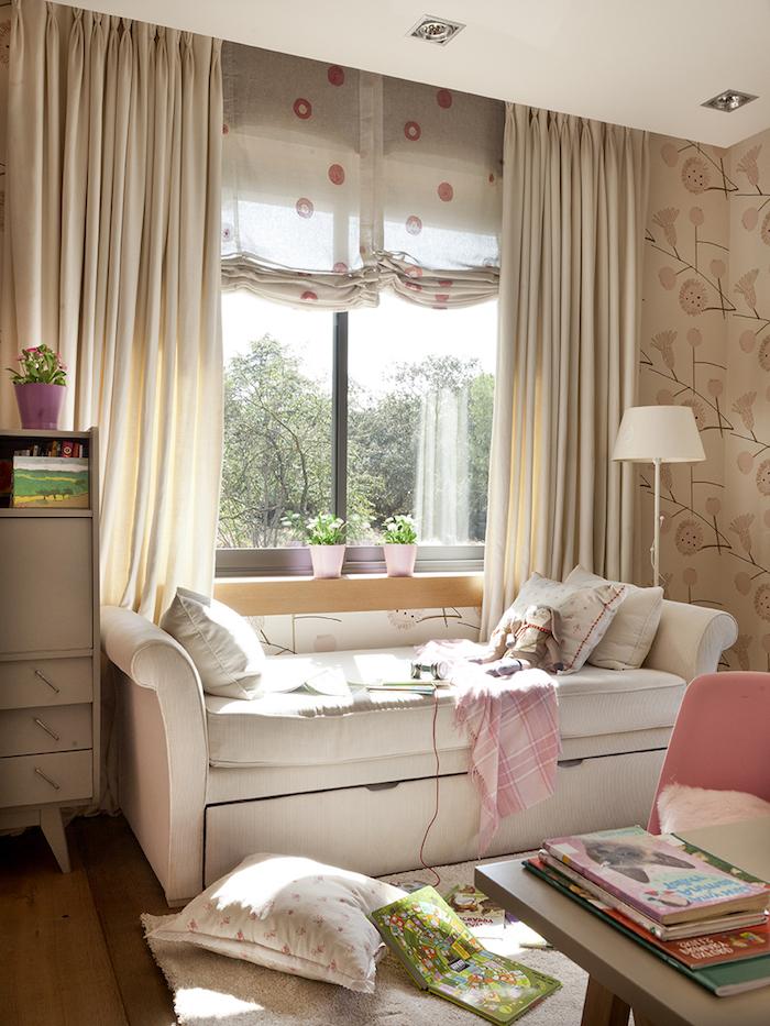 coin de lecture devant la fenêtre, banc en cuir blanc avec coussins décoratif, chaise rose pastel et bureau beige