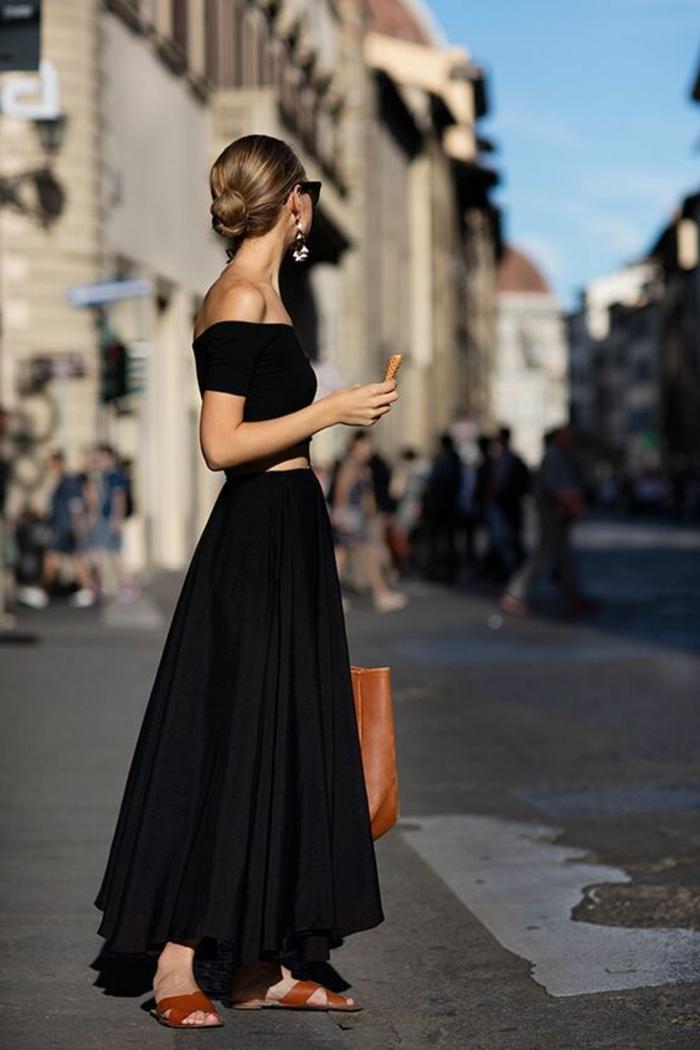 robe longue noire, chignon bas, lunettes de soleil, grand sac à main en cuir marron