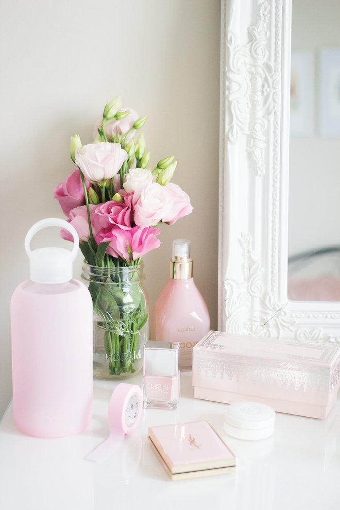 coin de beauté dans une chambre féminine, objets décoratifs en blanc et rose pastel, bouquet de roses