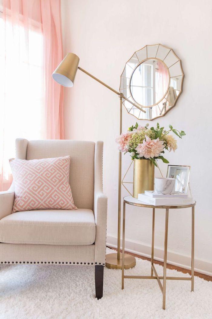 coin de repos dans le salon, miroir rond au cadre doré, objets décoratifs en cuivre, rideaux longs en rose pale