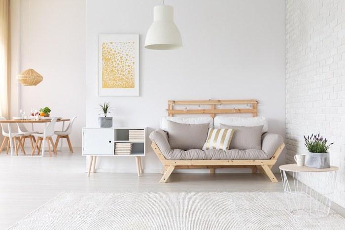 salle à manger ouverte sur un salon cocooning avec canapé en bois et coussin d assise grise, guirlande lumineuse, tapis blanc, rangement livres, mur en briques blaches