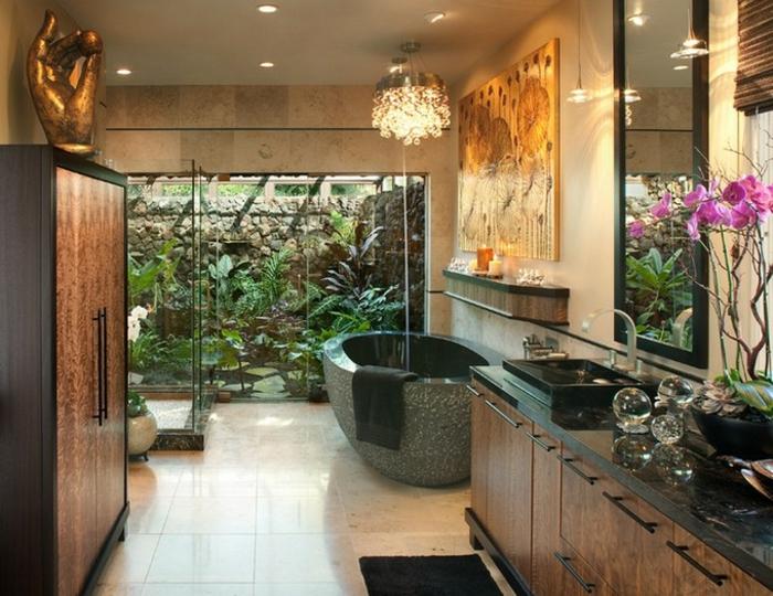 salle de bain nature, baignoire ovale en ciment, statuette originale, grande fenêtre avec vue plantes exotiques