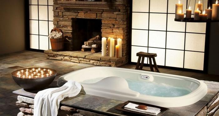 salle de bain zen, cheminée en pierre, bougies allumées, baignoire à encastrer, bol noir avec bougies flottantes