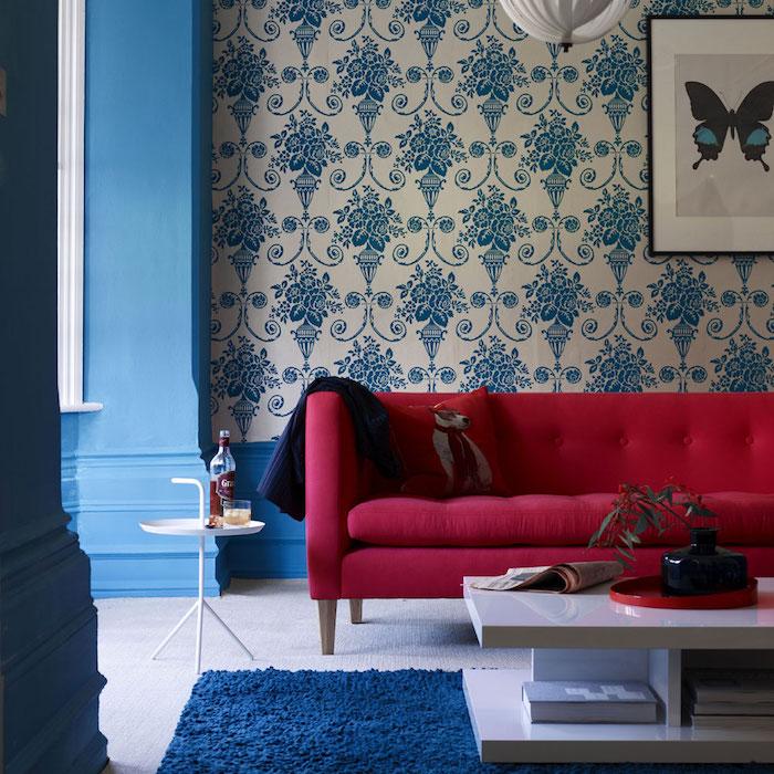 salon bleu et rouge, accord de couleurs, papier peint blanc à motifs floraux bleus, tapis bleu et table basse blanche, canapé rouge, ambiance vintage