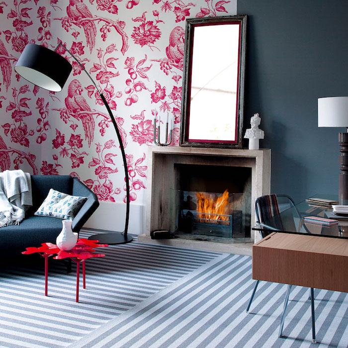 quelle couleur va avec le rouge, papier peint blanc à motifs exotiques rouges, cheminée en pierre, grand miroir, tapis zèbre à rayures blanc et gris, canapé gris anthracite, table basse rouge design