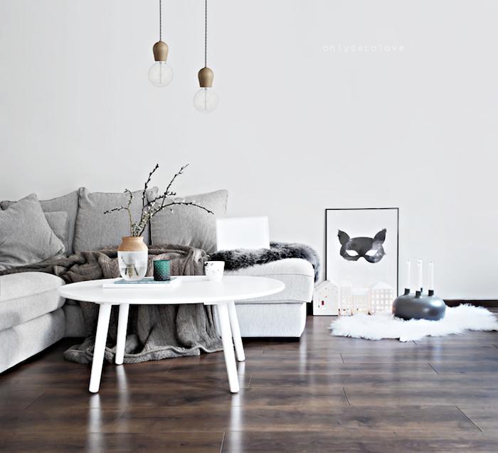 coussin cocooning, plusieurs coussins gris sur un canapé blanc table basse blanche et, tapis de fausse fourrure blanche, jeté gris, suspensions originales