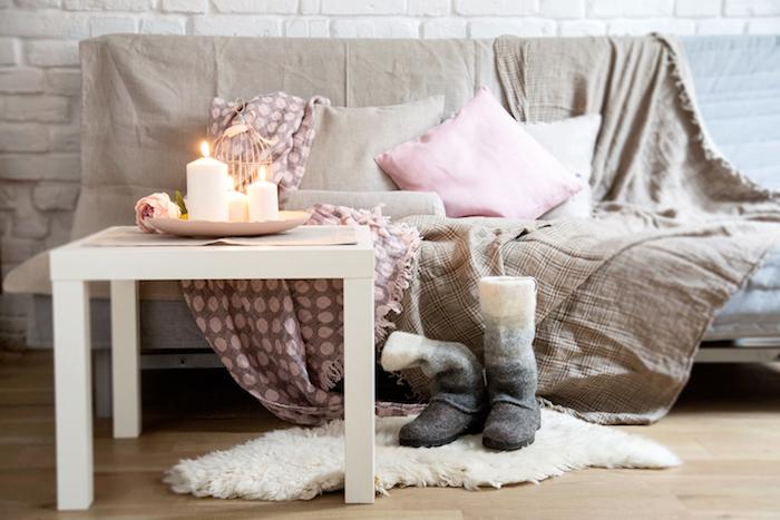 salon cocooning, avec canapé gris, couverture marron clair et rose, coussins decoratifs marron et rose, table basse blanche, tapis fausse fourrure, bougies romantiques
