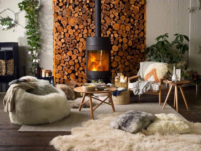 idée de salon cocooning chaleureux, cheminée moderne avec un fond de bûches de bois, tapis et fourrure beige, fauteuil blanc de peau animale, chaise et table en bois, parquet marron