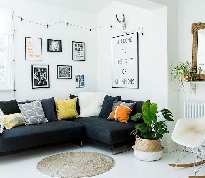salon cocooning blanc avec canapé noir, revêtement sol blanc, tapis rond, chaise scandinave avec jeté de fourrure, coussins decoratifs colorés, mur de photos en noir et blanc
