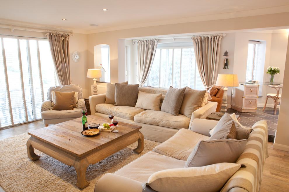 salon couleur lin, camaïeux de beiges, canapé, tapis, coussins beige avec accents gris et table basse en bois, plafond blanc