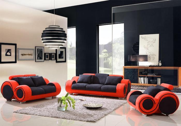 deco rouge et noir, canapés et fauteuil rouge et noir, tapis gris, carrelage blanc cassé, mur noir et blanc, suspension boule design
