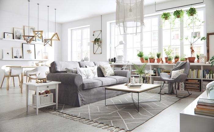 salle à manger ouverte sur salon gris et blanc, avec tapis scandinave et canapé gris, coin salle à manger blanc, étagère de rangement blanche, table basse minimaliste bois et metal, deco de plantes vertes