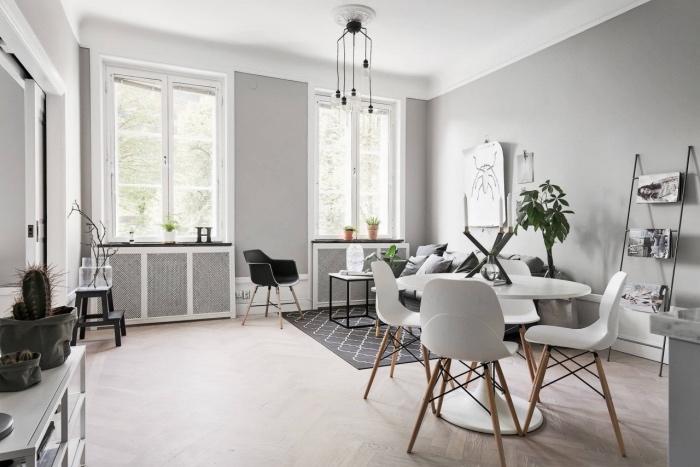 deco salon gris et blanc, mur couleur gris perle, coin salle à manger avec table blanche et chaises scandinaves, canapé gris, et tapis scandinave géométrique, mobilier scandinave gris et blanc
