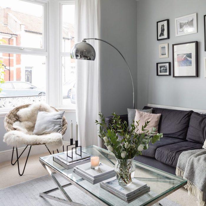 salon cocooning avec chaise en rotin et jeté de fausse fourrure, table avec plateau en verre, canapé gris anthracite, couverture grise, lampe sur pied grise