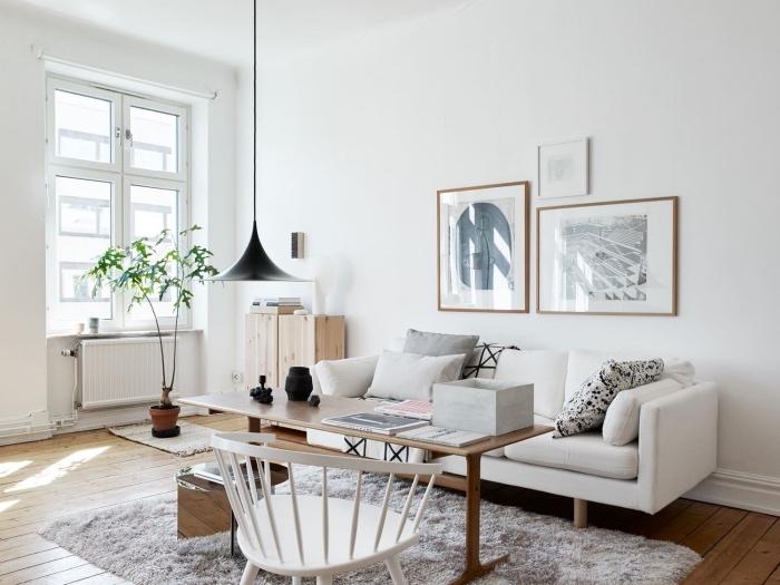 modele de salon scandinave blanc épuré, tapis gris, canapé blanc, coussins gris, blanc et noir, table en bois massif, chaise blanche, tapis scandinave, parquet clair