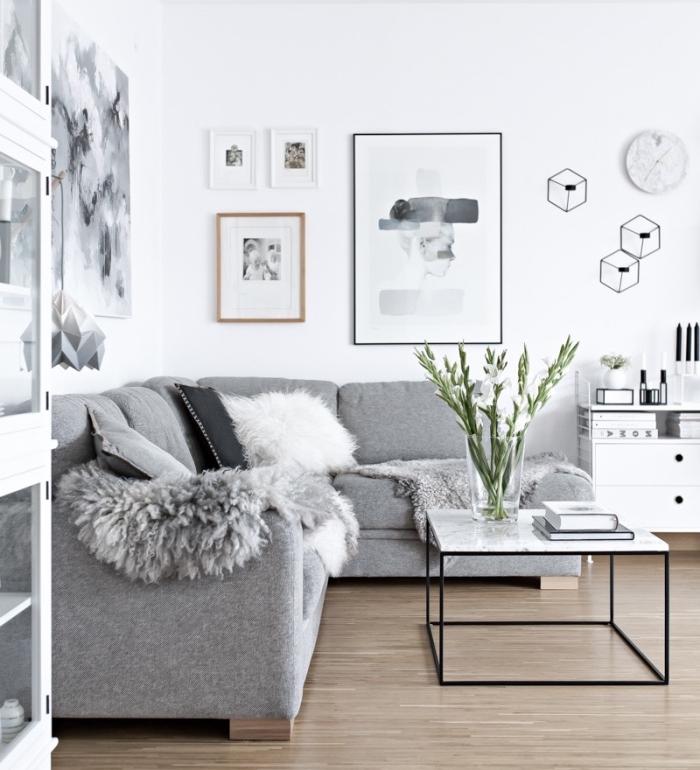 meuble scandinave canapé gris, peau animal grise, mur blanc, table basse en metal et plateau de marbre, deco murale noir et blanc, oeuvres graphiques