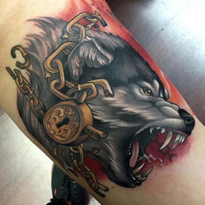 idée tatouage pour homme, dessin en encre sur jambe, tatouage en couleurs  loup féroce