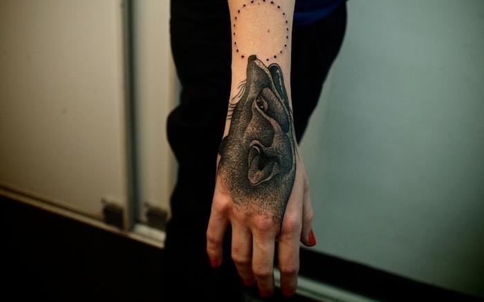 tatouage loup femme, manucure rouge et tatouage sur la main à design loup et lune