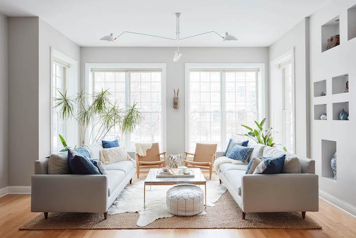 tapis cocooning dans un salon avec canapés gris, table basse, pouf blanc, chaises beiges, palmier, mur avec rangements intégrés