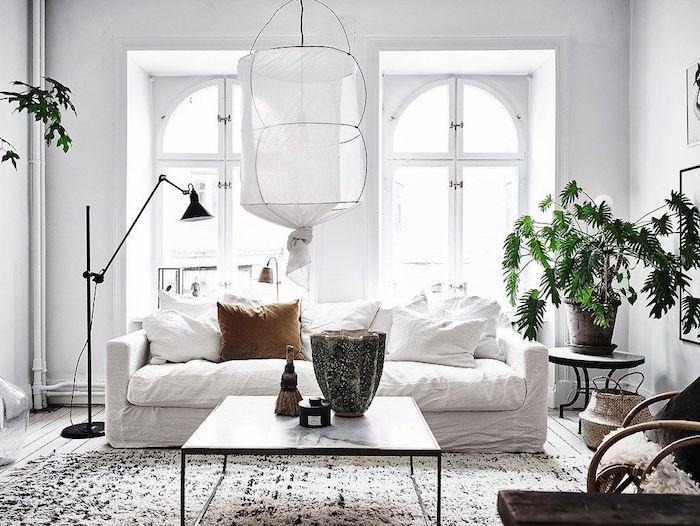 tapis cocooning en noir et blanc, table basse noire avec plateau de marbre canapé blanc, coussins blancs et marron, suspension originale, plante verte