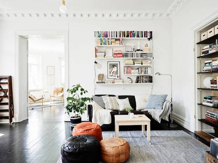 tapis cocooning, dans un salon blanc, étagère bibliothèque livres, canapé noir, coussins gris, blanc, table basse blanche à roulettes, poufs en cuir