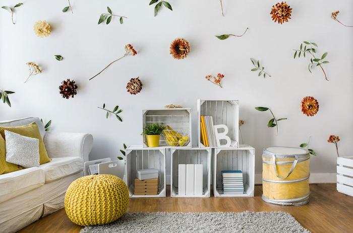 tapis cocooning moelleux, etagere cagette en bois blanc, canapé blanc avec coussins jaunes, pouf jaune, deco murale de fleurs artificielles