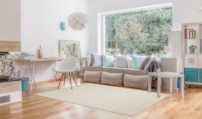 couleur peinture salon blanc, parquet clair, tapis couleur lin, canapé gris avec des coussins gris, blancs et bleus, bureau avec chaise scandinave