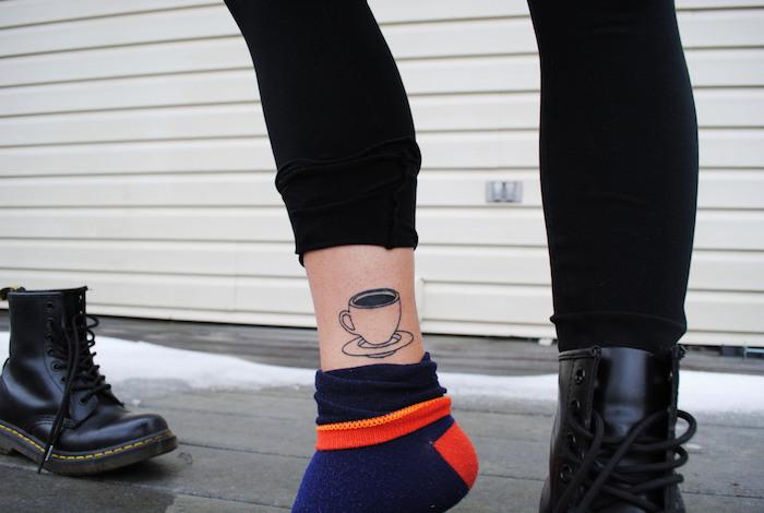 tatouage femme, dessin en encre à design tasse de café, bottines noires en cuir pour femme, pantalon noir