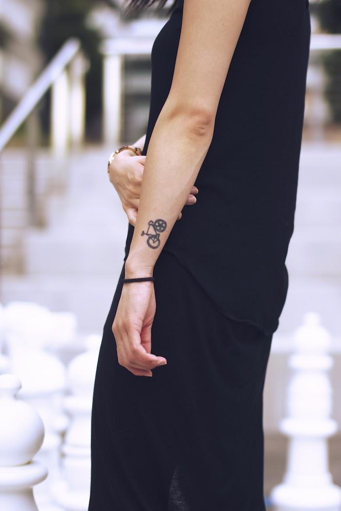 femme habillée tout en noir, bracelet en or, pantalon et débardeur pour femme, petit dessin en encre forme vélo