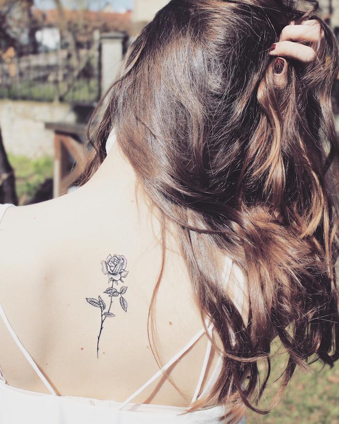 couleur de cheveux marron foncé, vernis à ongles bordeaux, robe blanche avec lacets sur le dos, petite rose gravée sur le corps