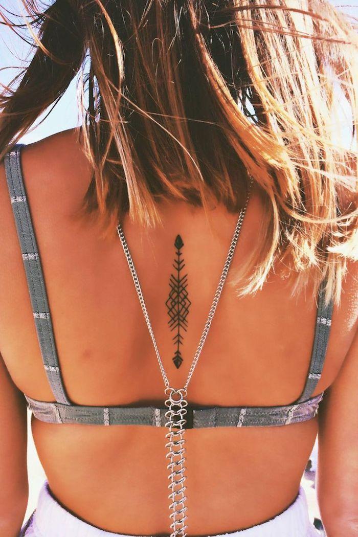 art corporel pour femme, dessin en encre motif flèche sur le dos, cheveux marron avec mèches blondes
