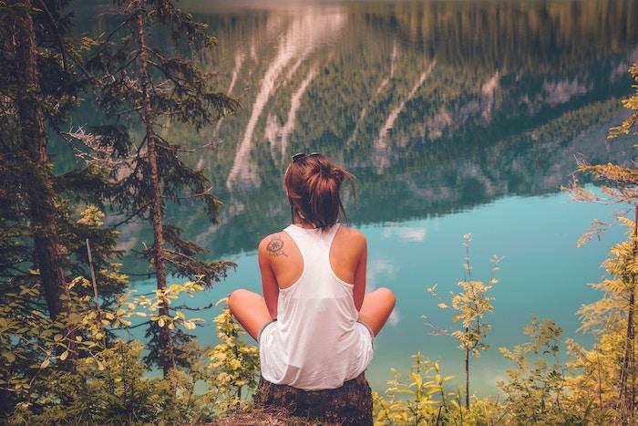 idée tatouage, lunettes de soleil noires modèle féminin, paysage naturel avec lac et montagnes, tatouage mandala sur l'omoplate