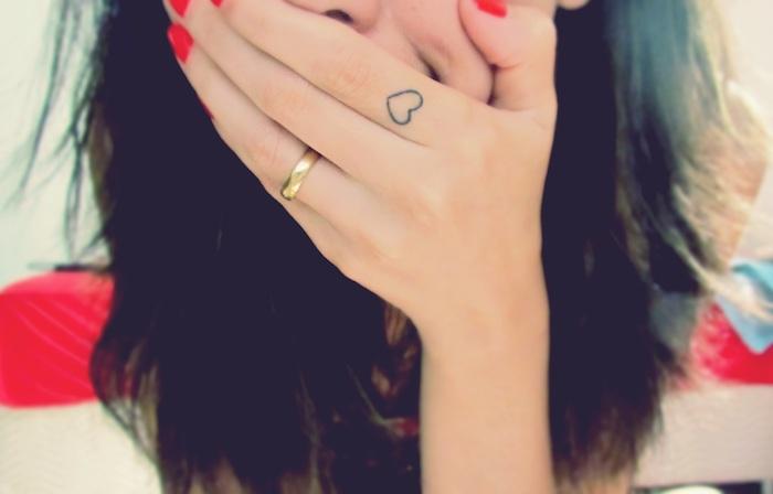 manucure rouge ongles courts, coupe de cheveux mi longs, petit tatouage coeur sur le doigt