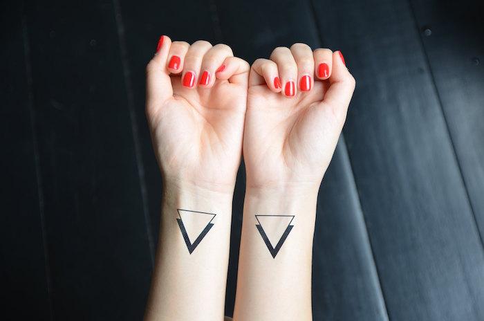 tatouage poignet femme, nail art rouge sur ongles courts, dessin en encre 3D avec triangles
