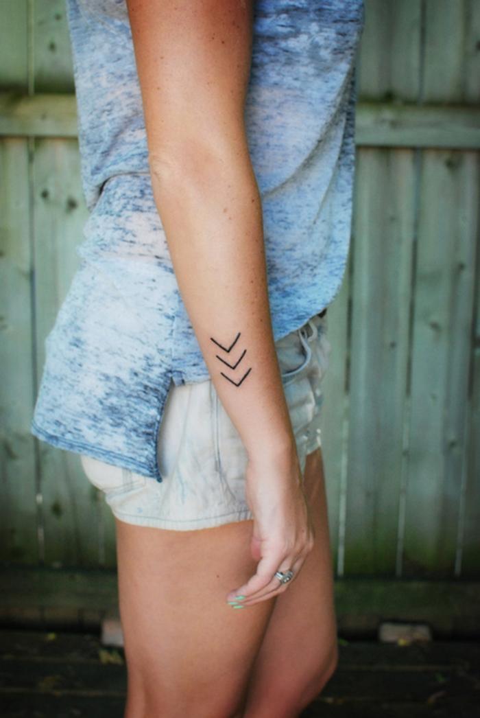tatouage femme sur le bras, t-shirt en bleu et blanc, shorts en blanc, ongles courts à vernis turquoise