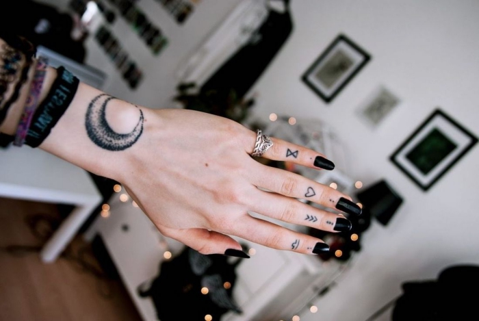 petit tatouage, dessin en encre sur les doigts, manucure noire, bague auriculaire femme