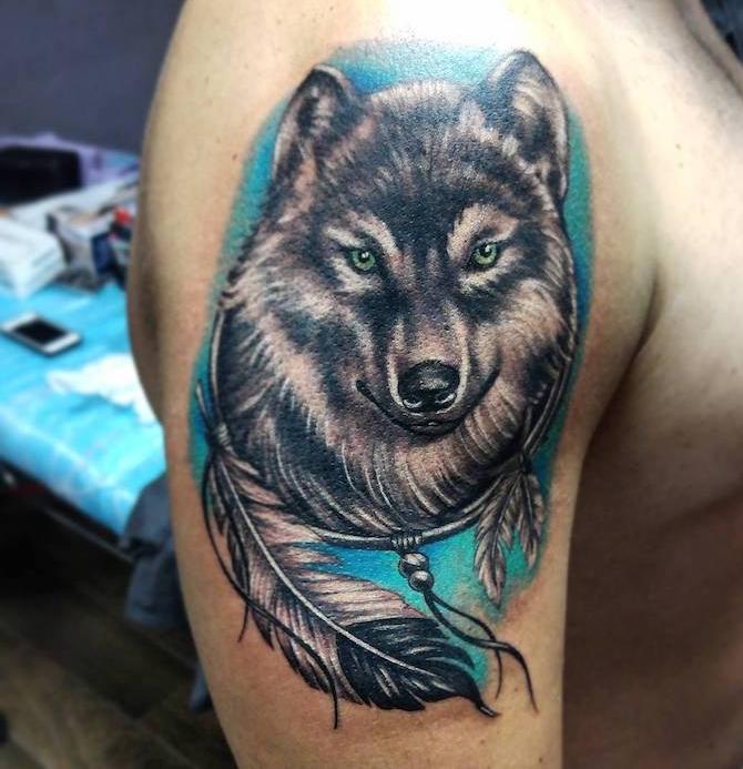 signification tatouage, dessin en couleurs sur l'épaule masculin, tatouge tête de loup avec plumes