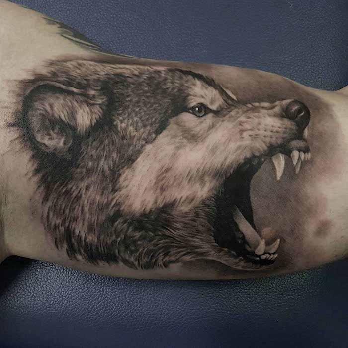 tatouage bras homme, dessin en encre à motif loup féroce, art corporel pour homme à dessin tête de loup